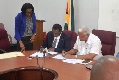 Minister of Agriculture Noel  Holder and FAO Representative Mr Ruben Robertson signs the four year country  program