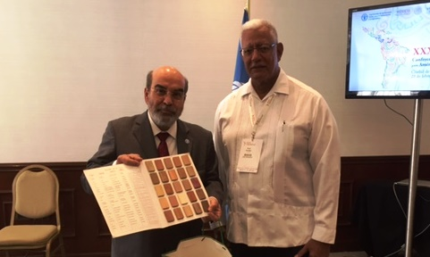 Minister Noel Holder with the  Director General of the FAO holding a gift presented by the minister
