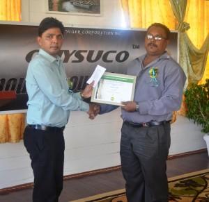 GuySuCo representative handing over award to Honour Roll Awardees