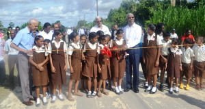 H.E. President Granger accompanied by Ministers of  Agriculture and Communities during the cutting of teh ribbon for one of the  commissioned access roads