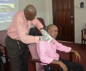 MOA staff demonstrating how to bandage a person with a neck injury during the Ministry's CPR and First Aid work shop