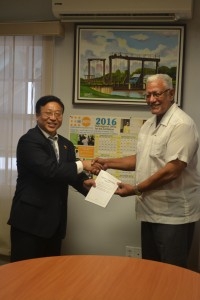 Ambassador Cui Jianchun hands over a copy of China's Policy Paper to Minister Holder