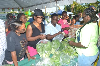 A group of buyers flock the GSA fresh produce booth.