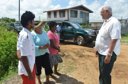 Minister Noel Holder chats with residents on his recent visit to Hope Estate.