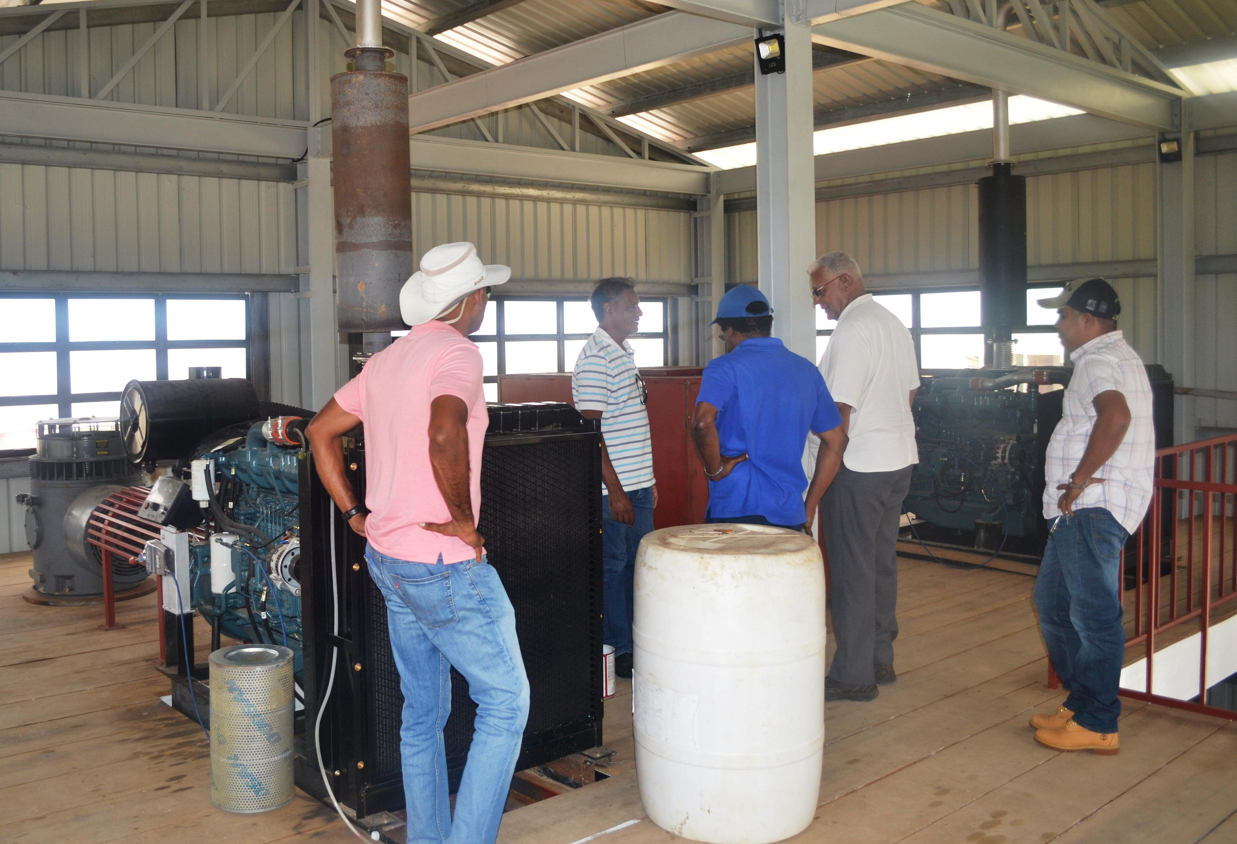 Minister Holder, NDIA CEO, Fredrick Flatts and other officials inspecting the pumps installed at the Lusignan Pump Station