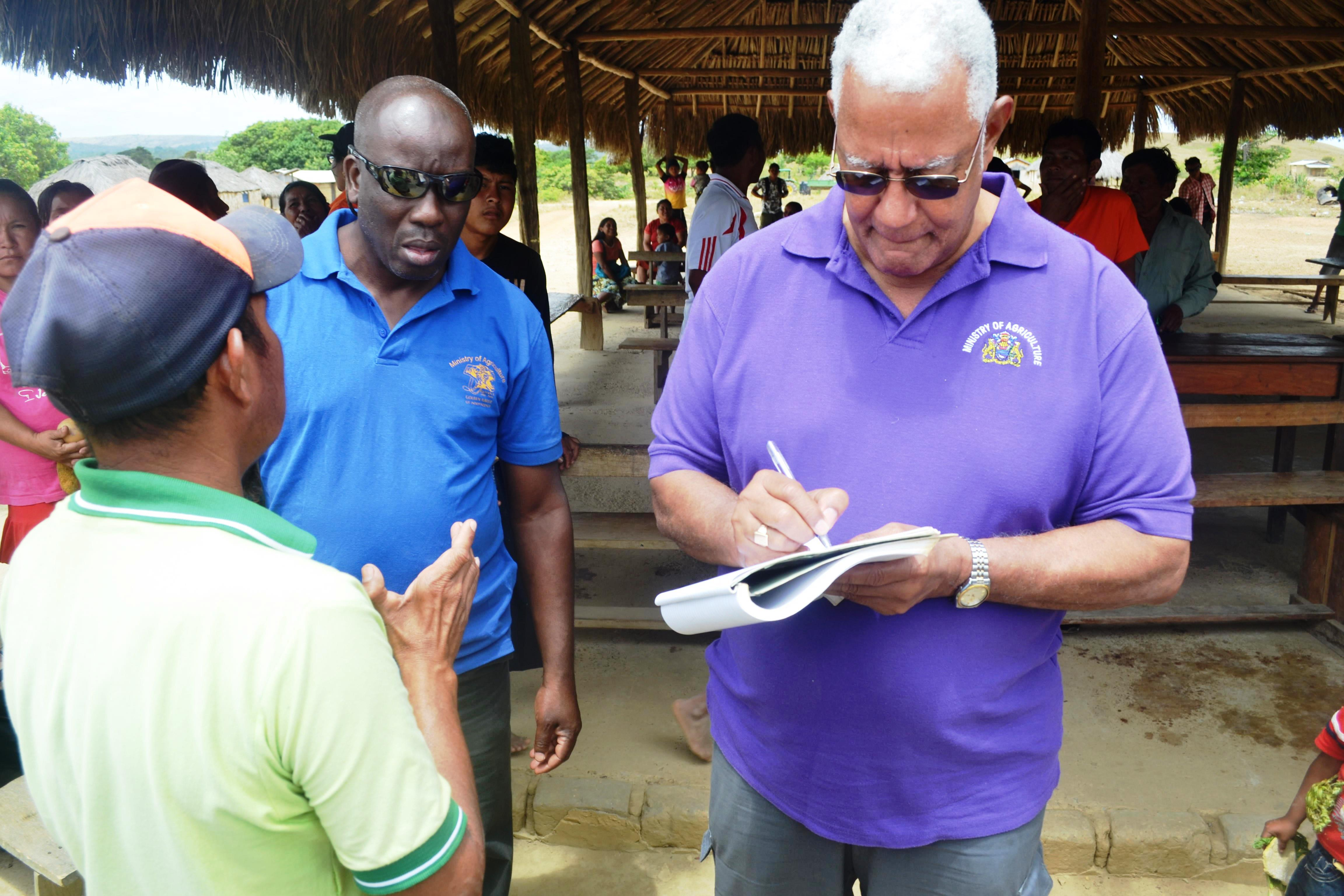 Minister Holder while collecting a report from the village toshao