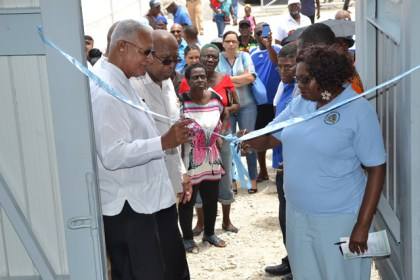 Minister Holder assists in the cutting of the ribbon to officially commission the pump station.