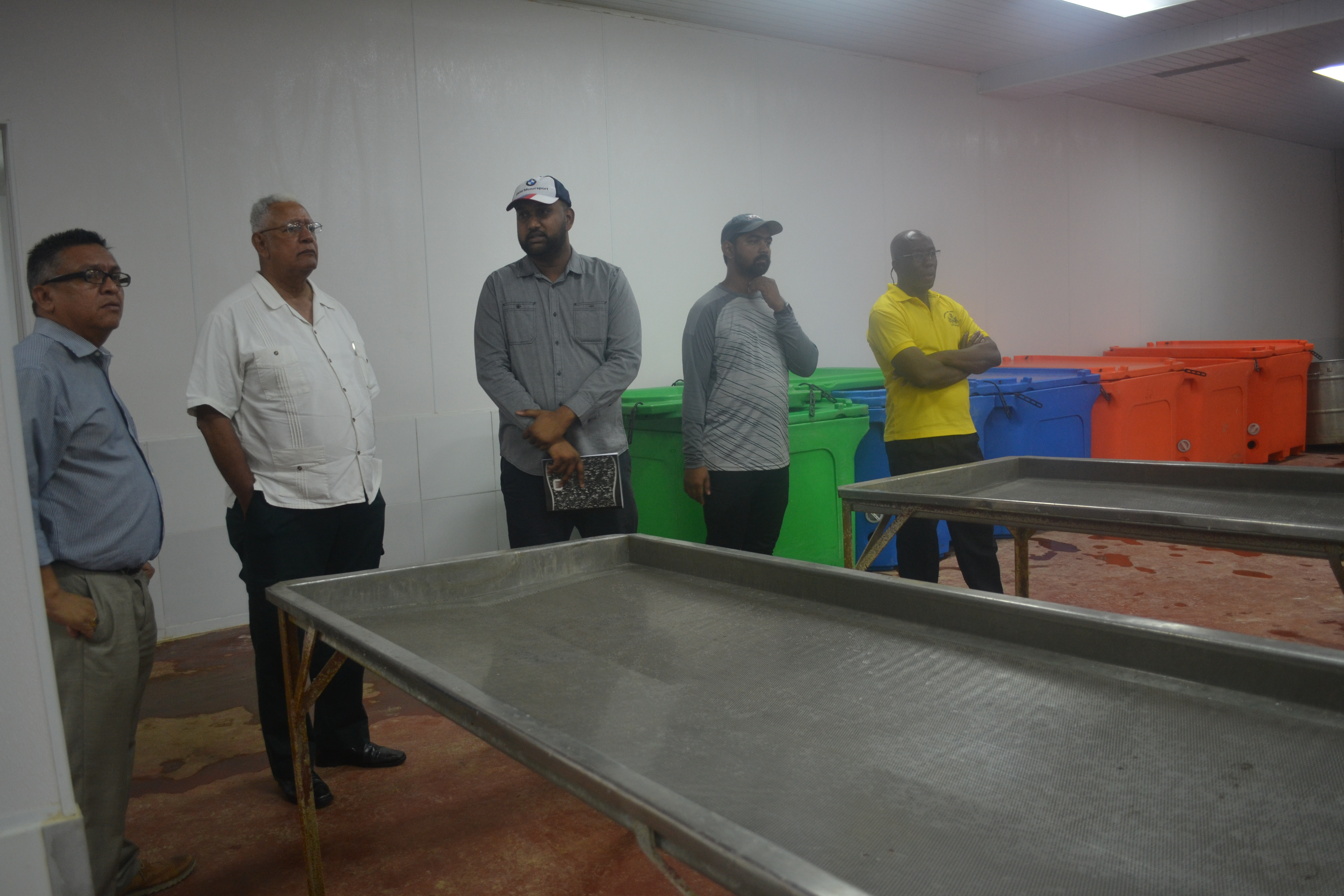 Minister Holder and other officials while touring Gopie Investments Inc's shimp processing facility