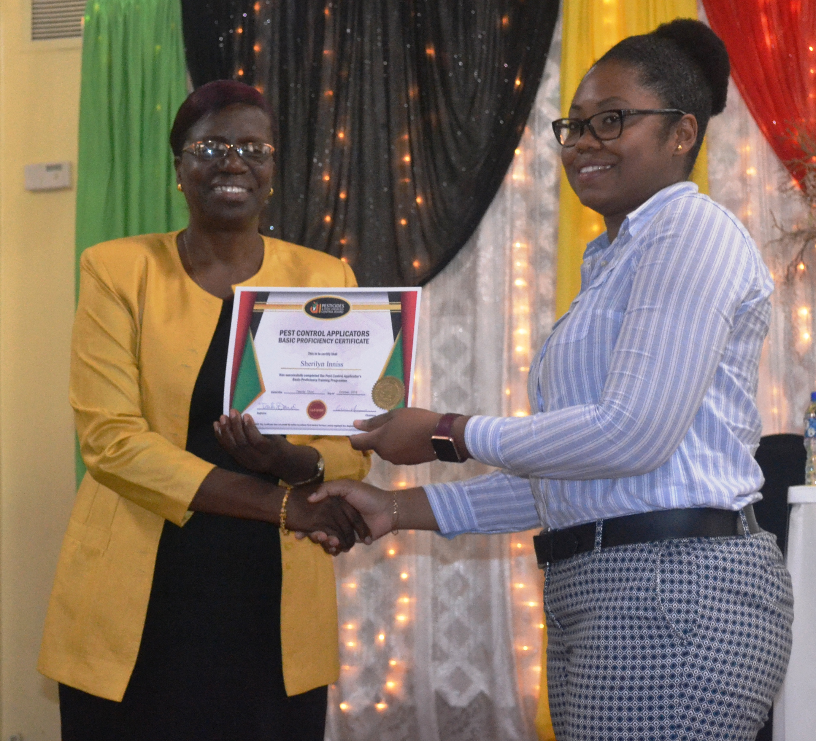 Ms. Sheriyln Innis recieving her certificate from the Permanent Secretary