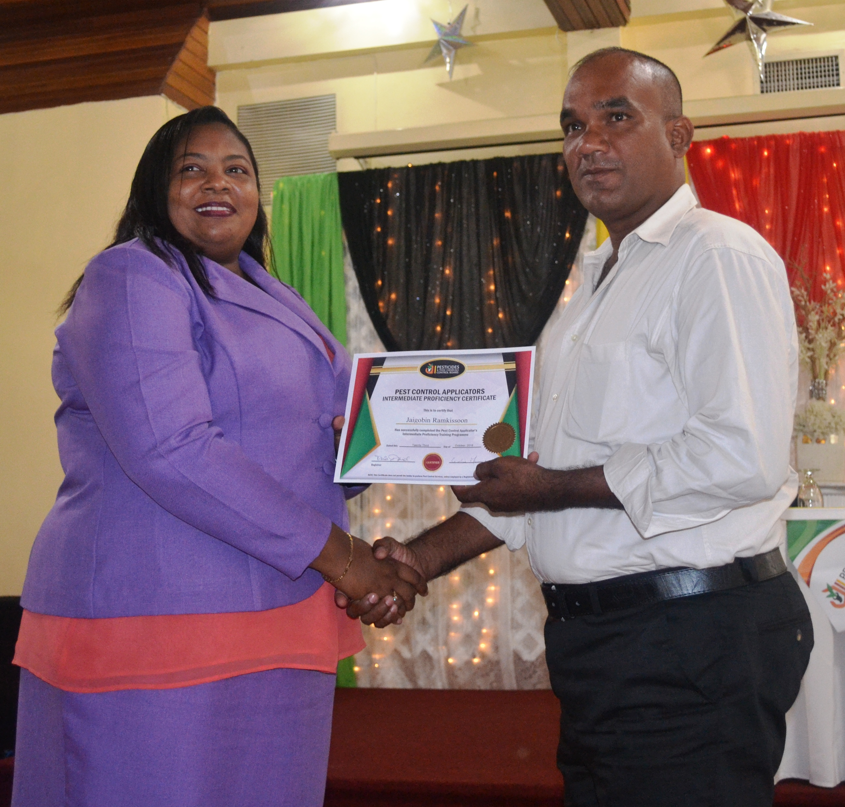 One of the graduates recieving their certificate from PTCCB Registrar, Trecia Garnath