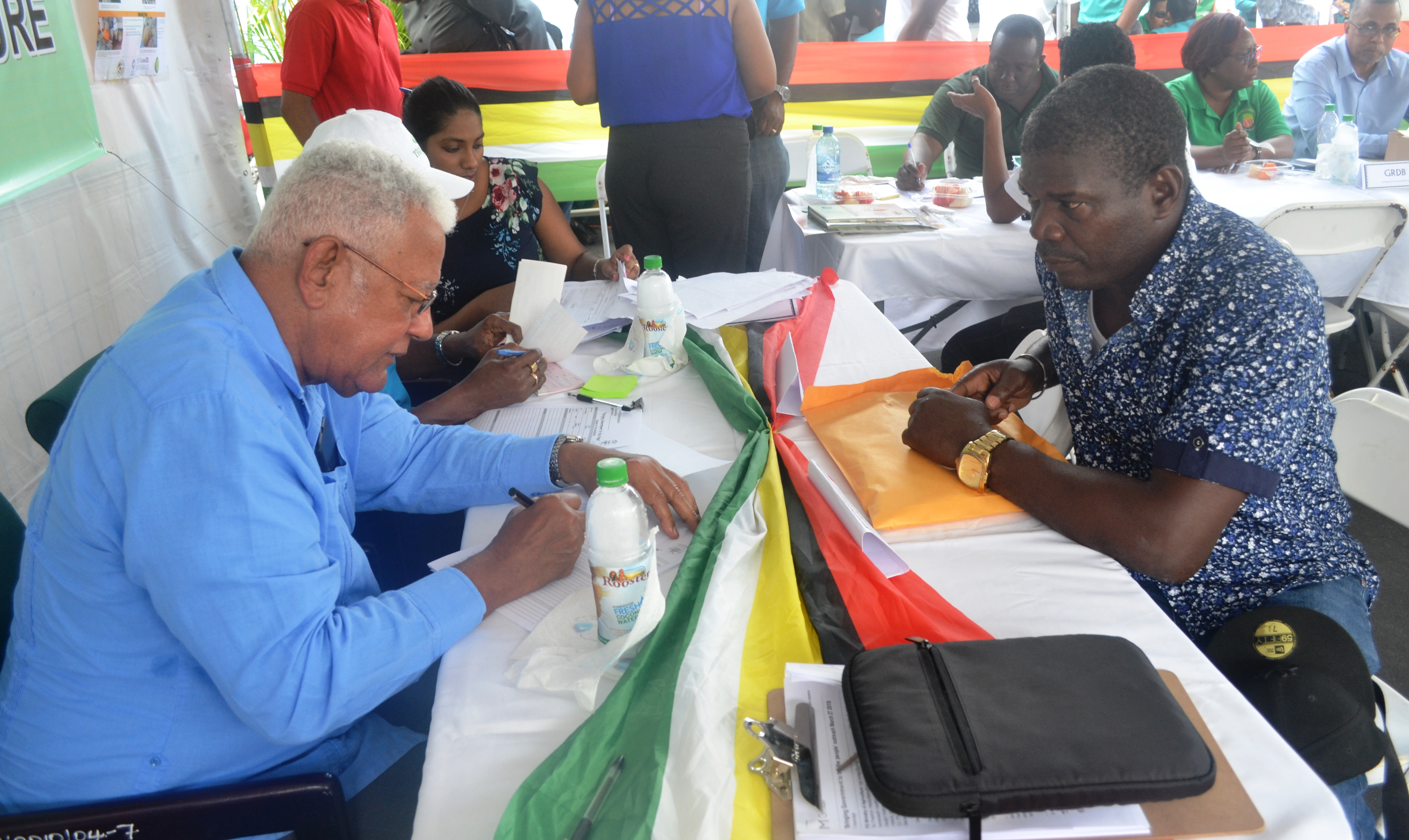 Agriculture Minister, Noel Holder during his engagement with an individual visiting the Ministry's booth