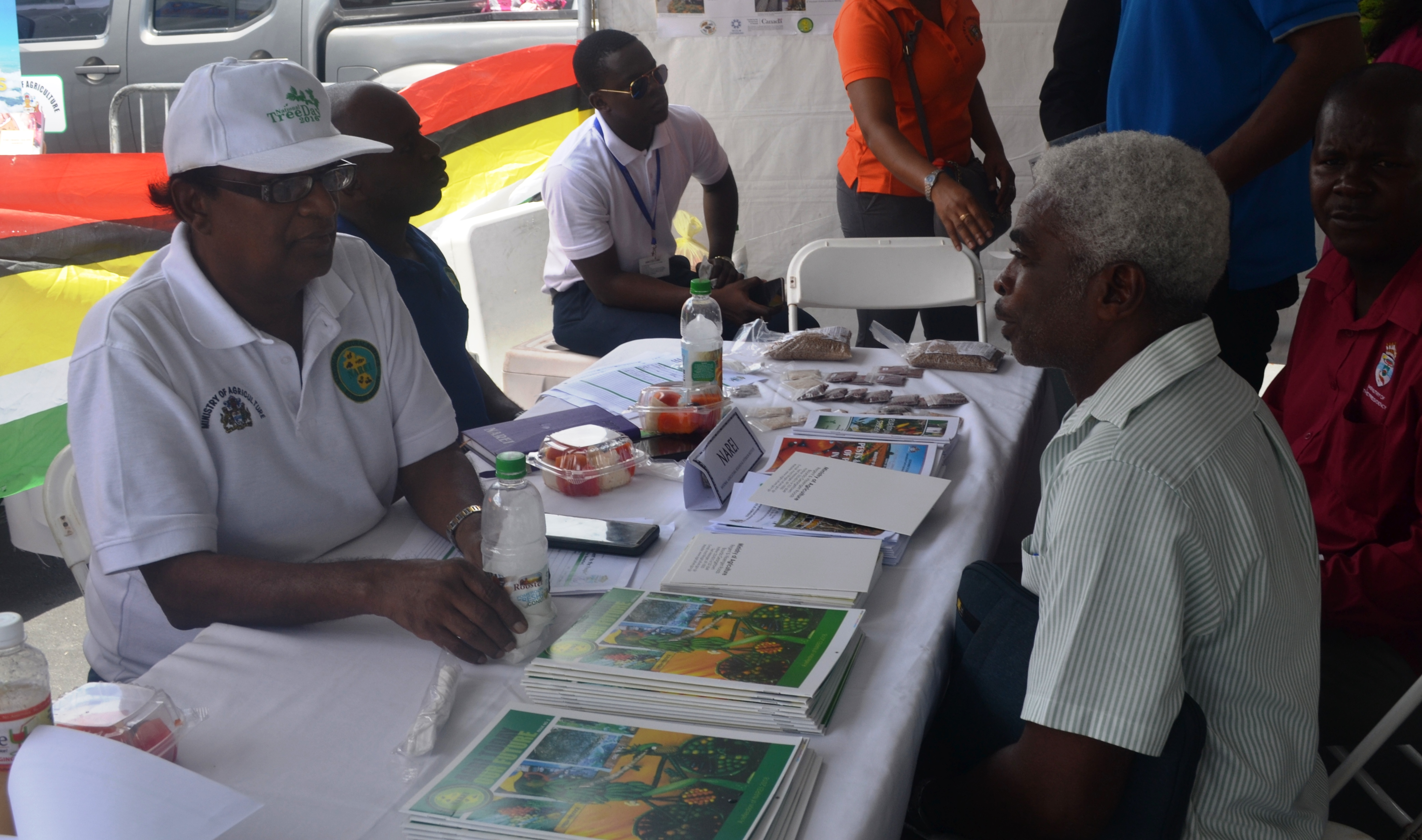 Dr. Oudho Homenauth while engaging an individual that visited the ministry's booth