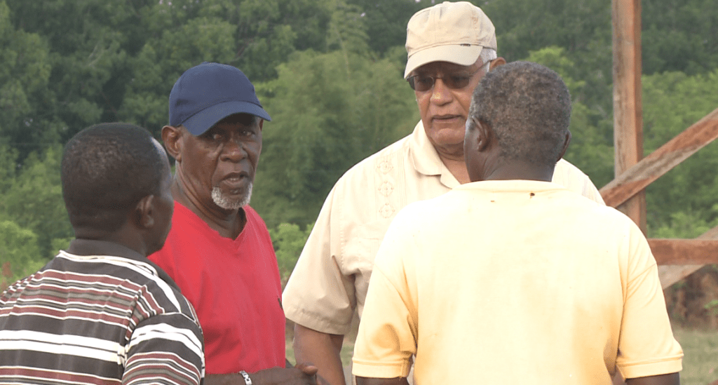 Minister of Agriculture Noel Holder interacts with residents during his walkabout.