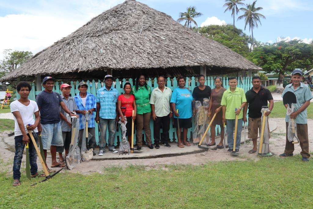 Minister Adams-Yearwood pictured with the villagers and some of the donated gardening tools
